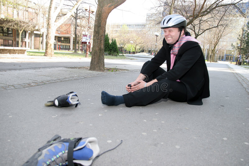 Pain. Businessman in a lot of pain from roller-blading stock images