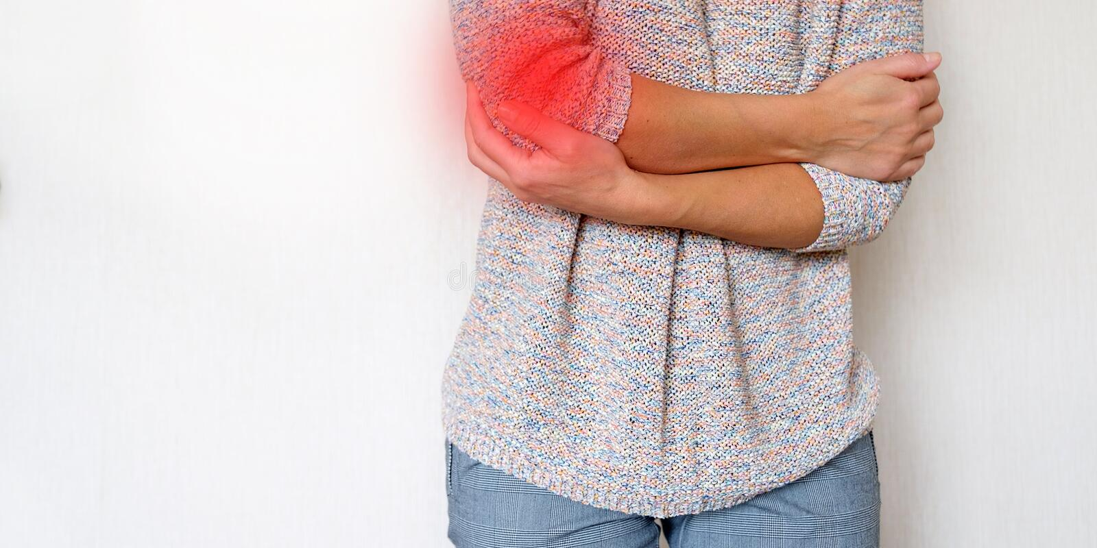 Pain area red background. The girl grabbed his hand in pain. Suffers from diseases of the joints royalty free stock images