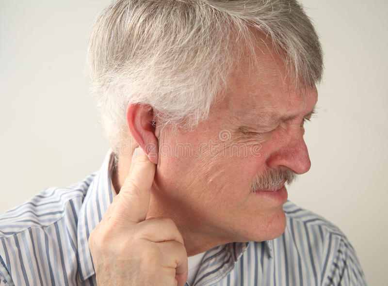 Pain around the ear. A senior man suffers from pressure behind his ear royalty free stock photography