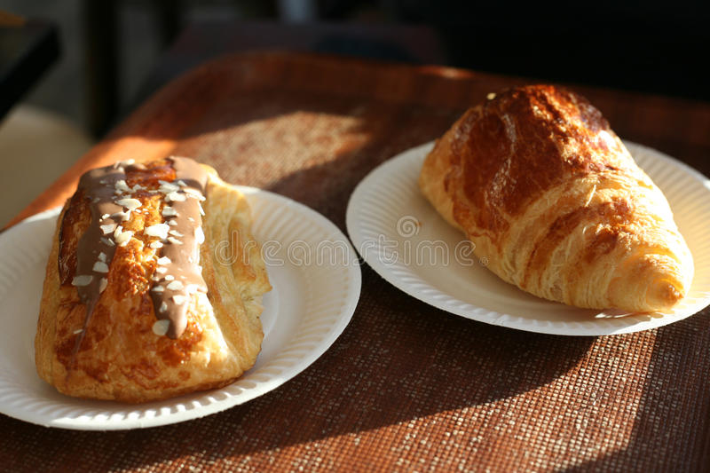 A duo of fresh croissants. Pain au chocolat and traditional European croissant stock images