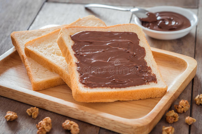 Pain avec de la crème de chocolat du plat en bois photos libres de droits