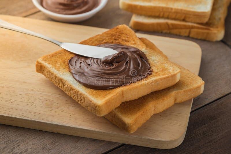 Pain avec de la crème de chocolat du plat en bois photos stock