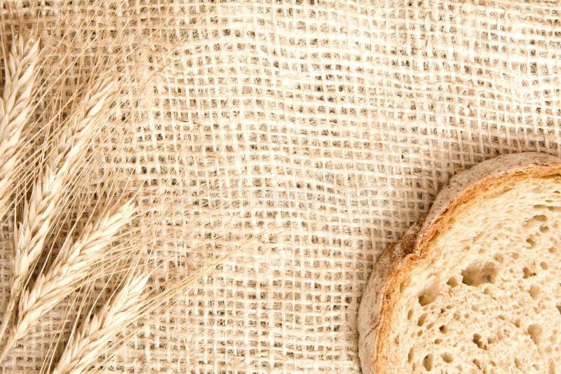 Pain avec du blé sur le fond de toile de jute images stock