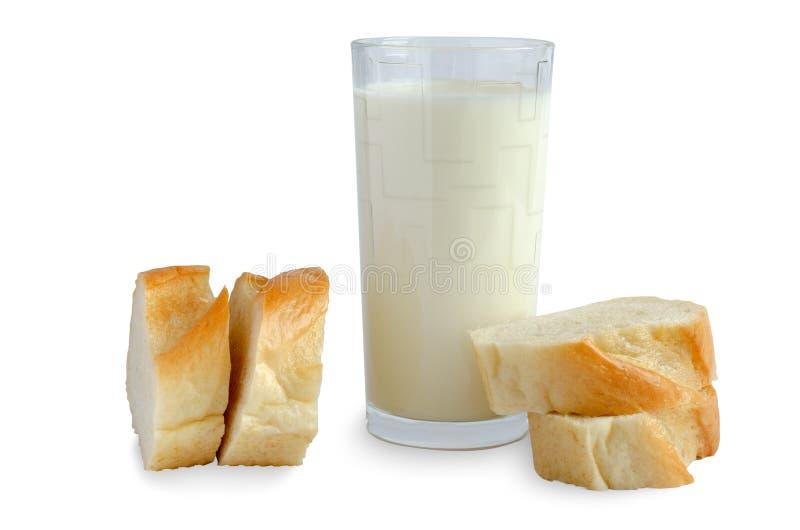 Pain blanc, lait dans un verre sur le fond blanc image stock