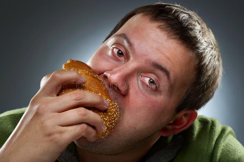 Pain blanc mangeur d'hommes corpulent affamé photo stock