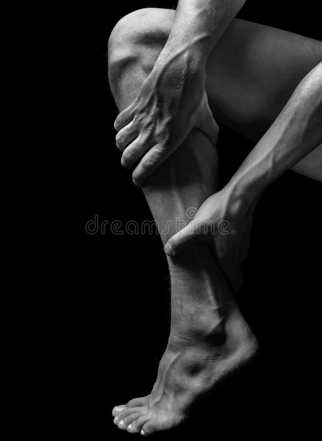 Pain in the calf muscle. Acute pain in the male calf muscle, black and white image royalty free stock photos