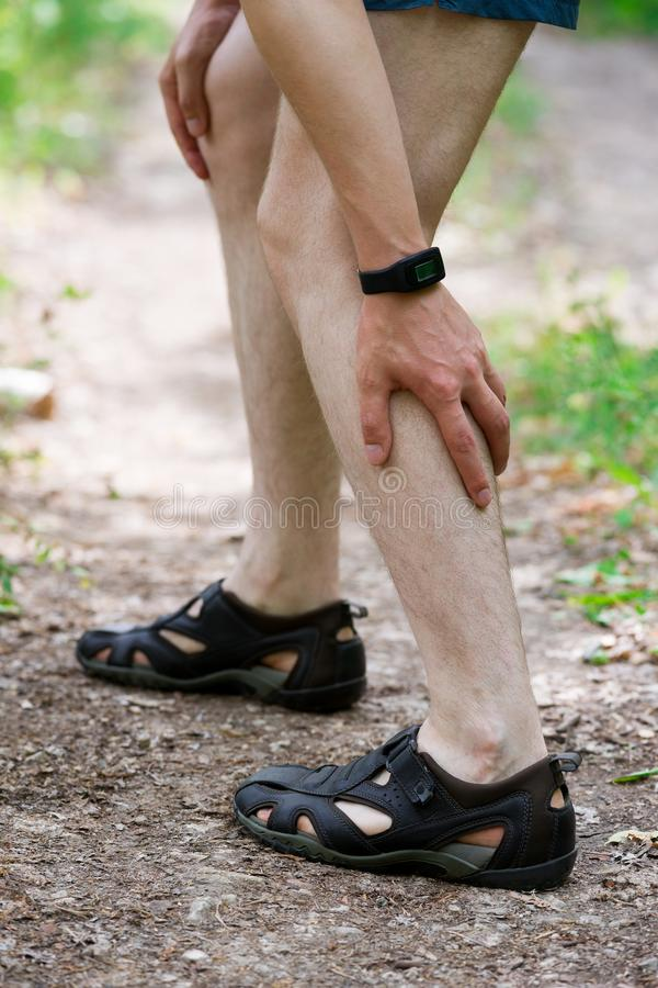 Pain in calf muscle, sprains on the leg, massage of male foot, injury while running, trauma during workout. Outdoors concept royalty free stock images