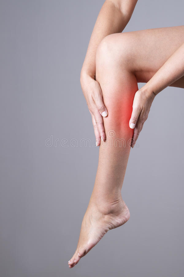 Pain in the calf muscle of the woman. Massage of female feet. Pain in the human body on a gray background. With red dot stock photography