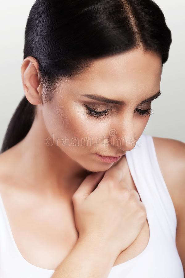 Pain. Close-up of a young woman feels severe chest pain. Close-up of a woman`s body with a hand on her chest. The girl suffers fr. Om a painful feeling that has stock photo