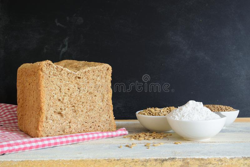 Pain complet sur une nappe à côté de farine et de céréales contre un tableau noir image libre de droits