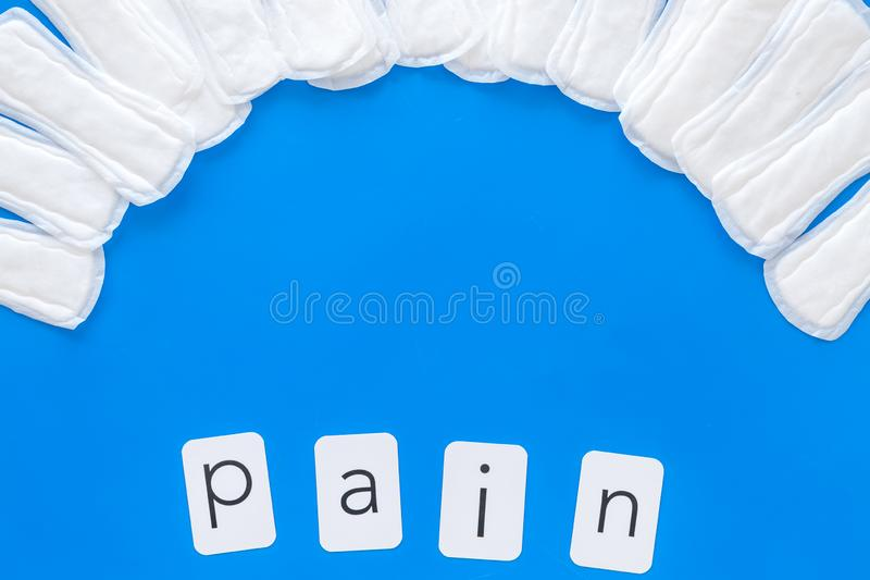 Pain copy for menstrual period concept with sanitary pads on blue background top view space for text royalty free stock photo