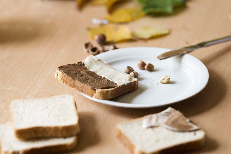 Pain coupé en tranches dans le plat avec de la crème et des écrous de chocolat image stock