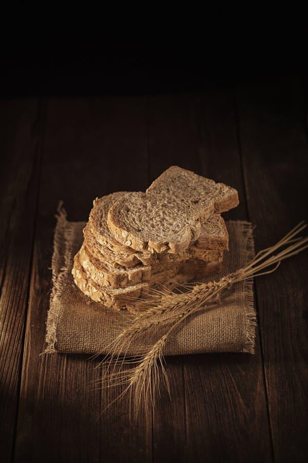 pain coupé en tranches de blé entier sur la table en bois, fond foncé photographie stock libre de droits