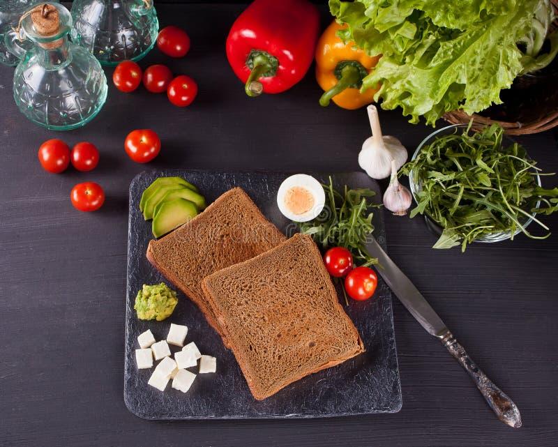 Pain coupé en tranches de pain grillé de plat noir avec des légumes Vue supérieure photographie stock
