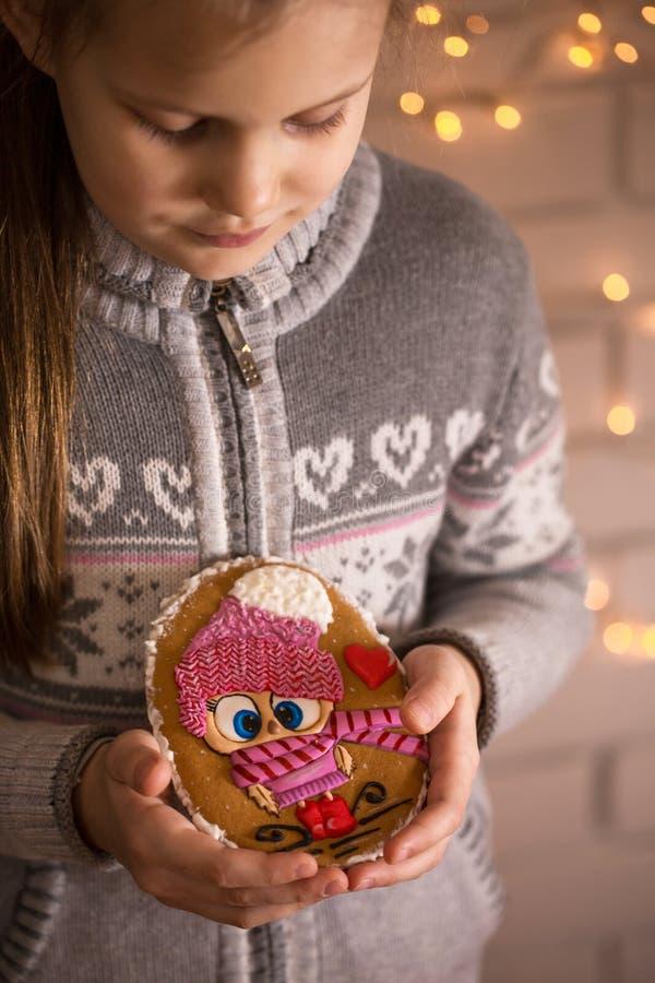 Pain d'épice chez les mains des enfants images stock
