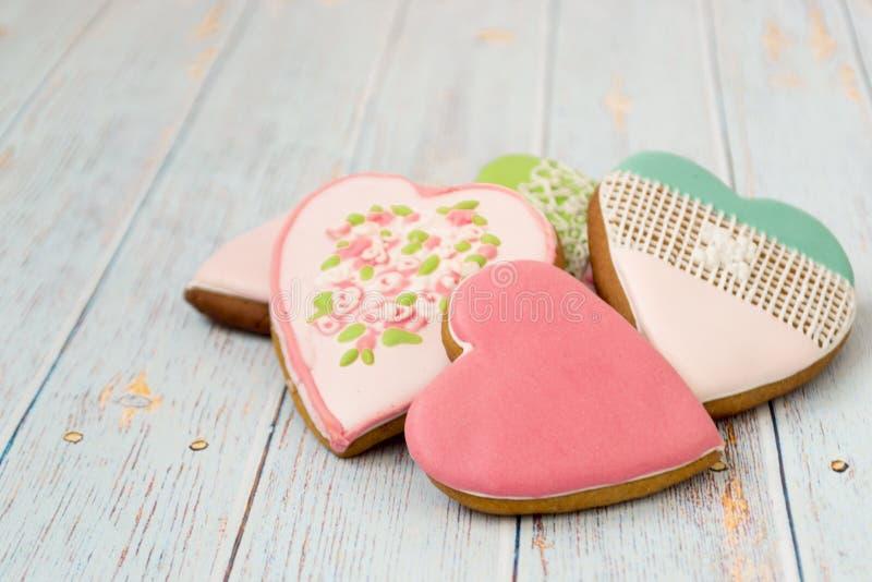 Pain d'épice peint sur un fond en bois clair Biscuits savoureux dans un forepe des coeurs photographie stock libre de droits