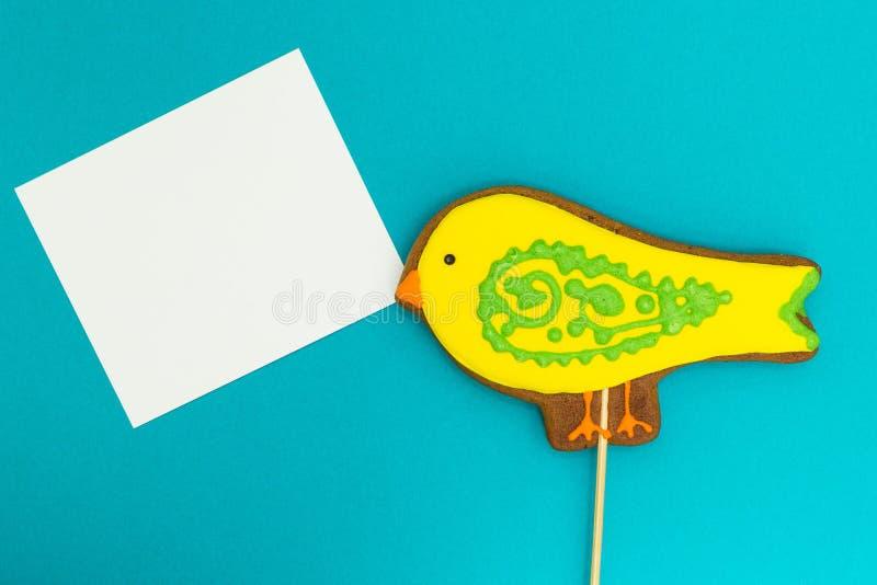 """Pain d'épice sous forme de """"oiseau """"jaune avec une feuille blanche sur un fond bleu, l'espace pour le texte photo libre de droits"""