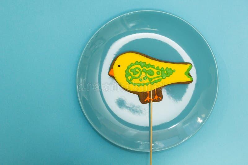 """Pain d'épice sous forme de """"oiseau """"jaune dans un plat bleu sur un fond bleu photographie stock libre de droits"""