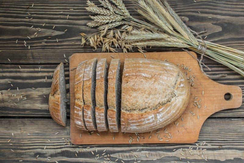 Pain d'un mélange de farine découpé en tranches sur un fond en bois photographie stock libre de droits