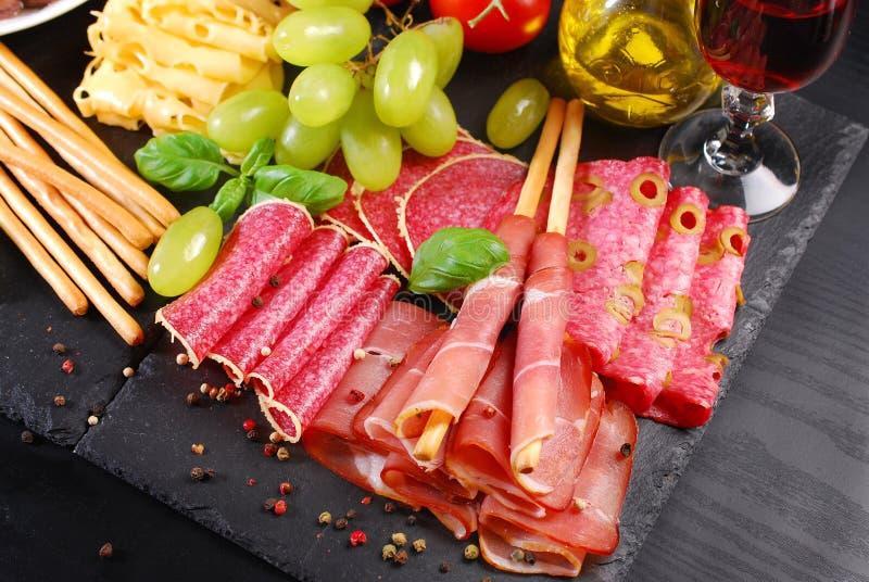 Pain de bâton de Grissini avec du jambon sur le conseil noir avec des apéritifs photo libre de droits