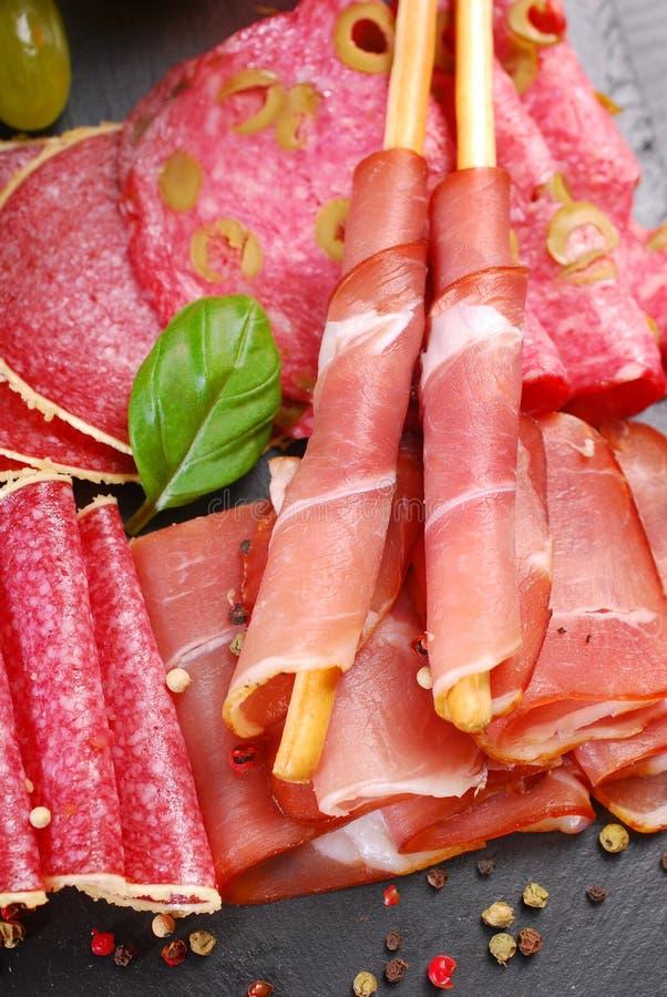 Pain de bâton de Grissini avec du jambon sur le conseil noir avec des apéritifs photos stock