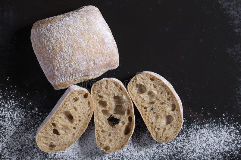 Pain de pain de ciabatta et coupé en tranches sur un fond noir photos stock