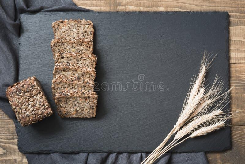 Pain de forme physique Un pain de pain de seigle entier rustique frais avec du blé, coupé en tranches sur un plat et un panneau n photo libre de droits