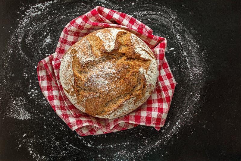 Pain de pain frais sur le fond noir Pain sur la serviette à carreaux rouge Concept de boulangerie Type rustique photos stock