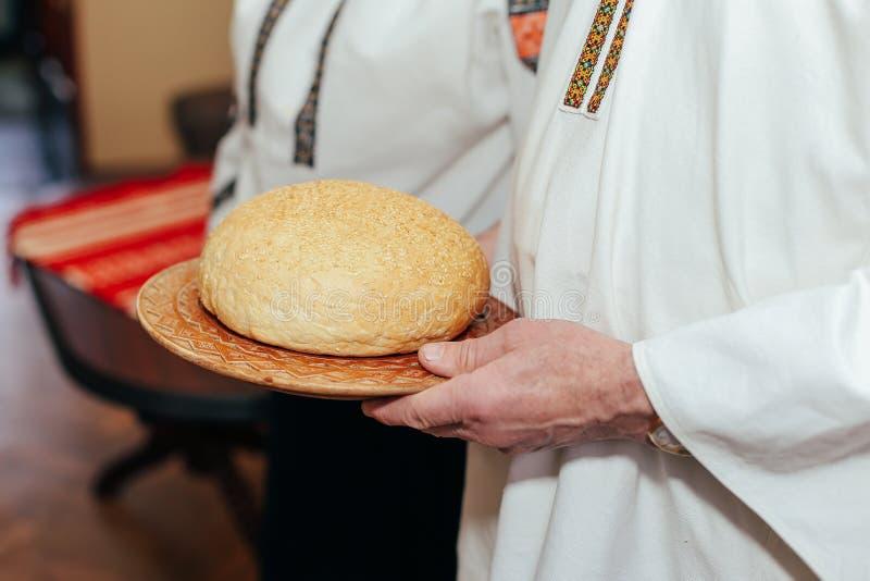 Pain de mariage Les parents tiennent le pain dans leurs mains photographie stock