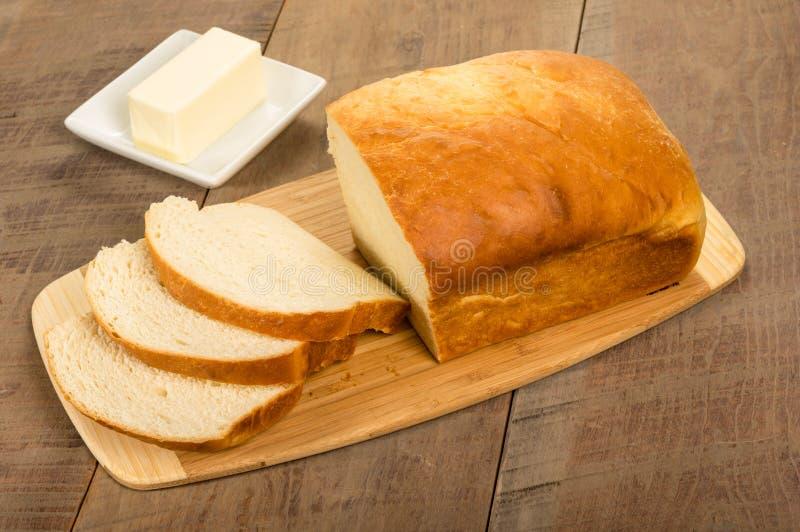 Pain de pain coupé en tranches avec le plat de beurre photos libres de droits