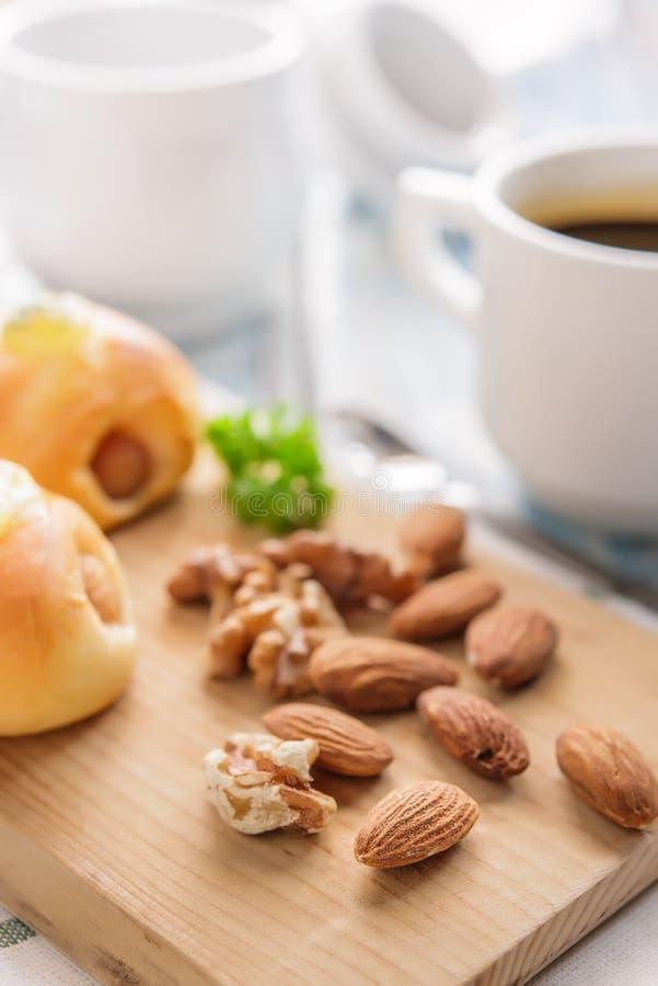 Pain de petit déjeuner avec des amandes et des noix, et jui de thé ou d'orange image stock