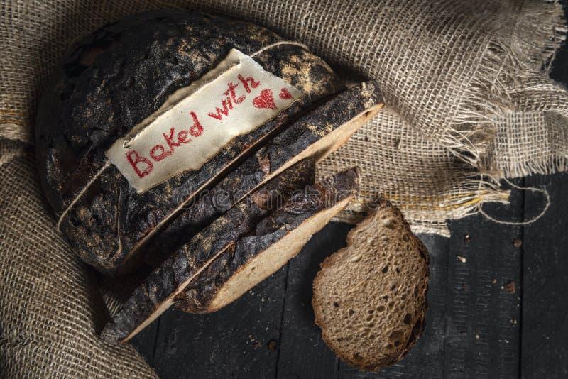Pain de seigle de Brown et cuit au four avec le label d'amour Pain allemand traditionnel sur le tissu de jute images stock