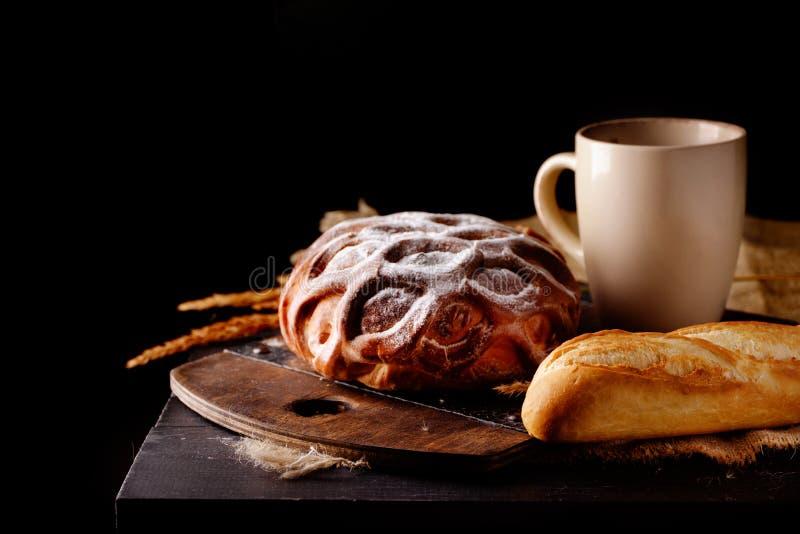 Pain doux du pain blanc en poudre avec du sucre, tasse de lait, pain de pain français sur un fond foncé image stock