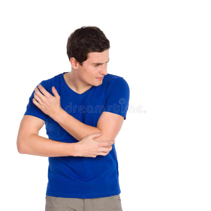 Pain in an elbow. Close up of young man massaging elbow in pain. Three quarter length studio shot isolated on white stock photography