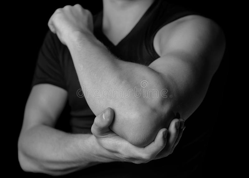 Pain in the elbow joint. Man holds his the elbow joint, acute pain in the elbow, black and white image stock photography