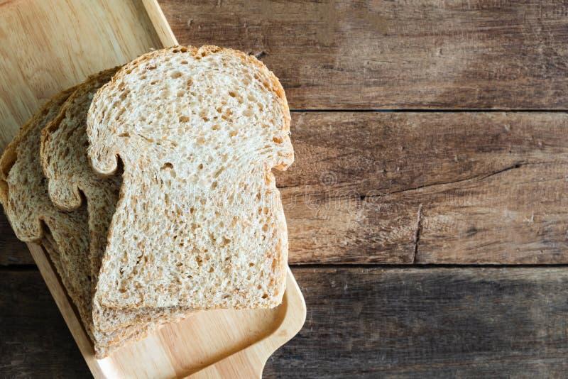 Pain empilé de sandwich à blé entier de tranche de plat en bois sur la table en bois photo libre de droits