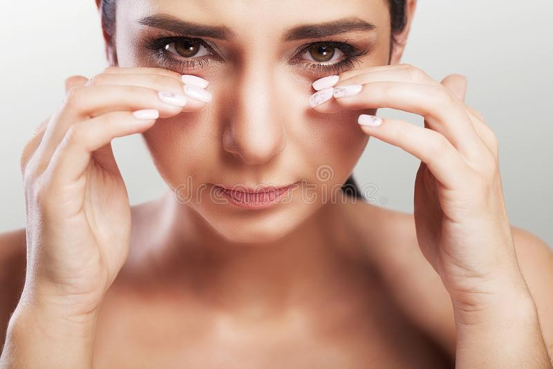 Pain in the eye area. A beautiful unhappy woman who suffers from severe pain in the eye area. Portrait of a sad woman`s feeling o stock image
