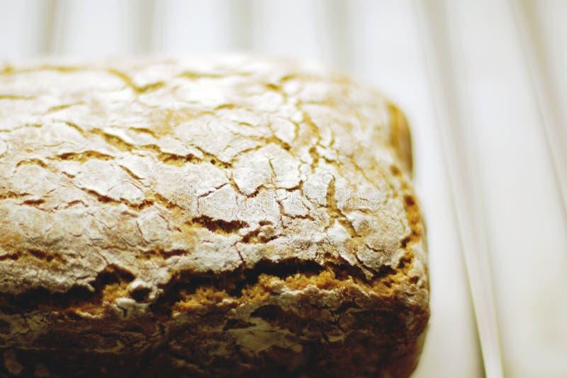 Pain fait maison ?ooling vers le bas sur le support en métal, texture criquée de croûte de pain en farine image libre de droits