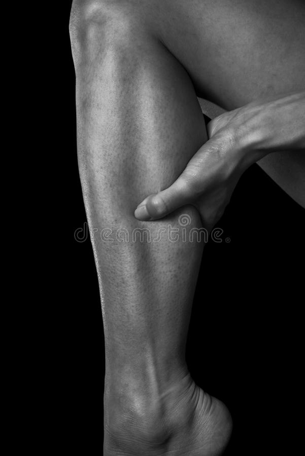 Pain in the female calf muscle. Black and white image stock photo