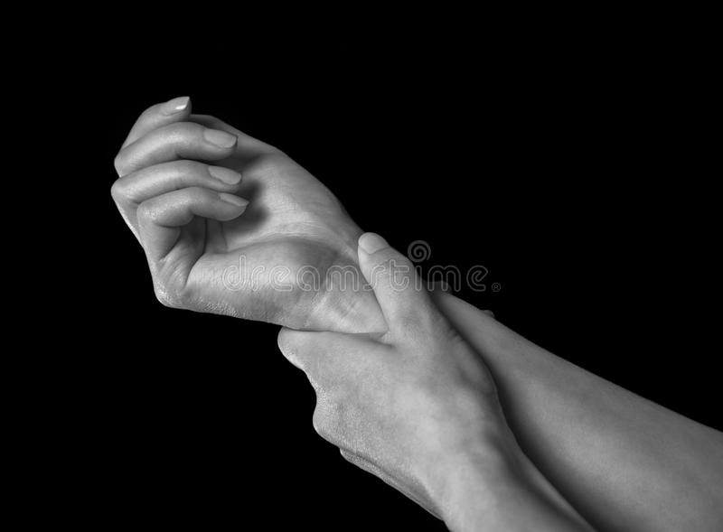 Pain in the female wrist. Unrecognizable woman holds her hand, pain in the wrist, black and white image royalty free stock image