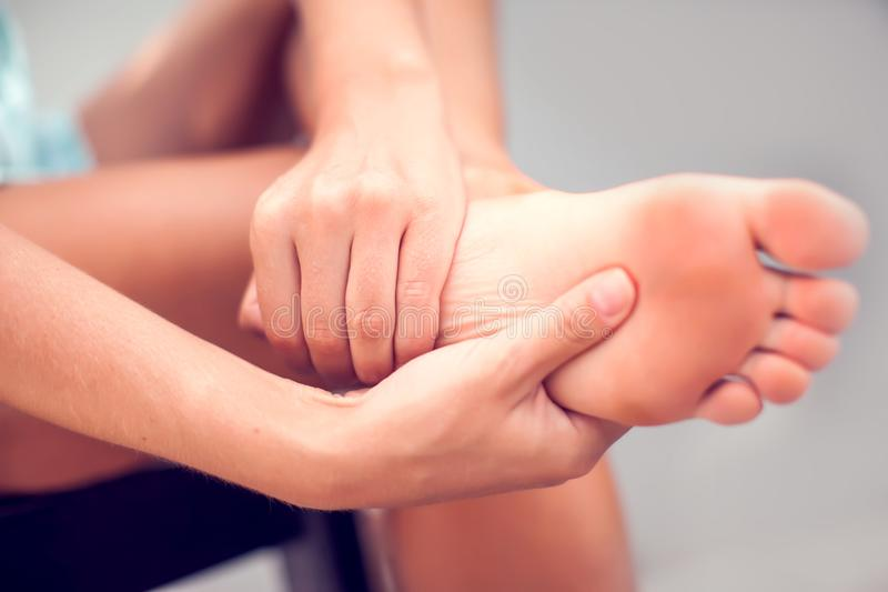 Woman hand holding foot with pain, health care and medical concept stock photography