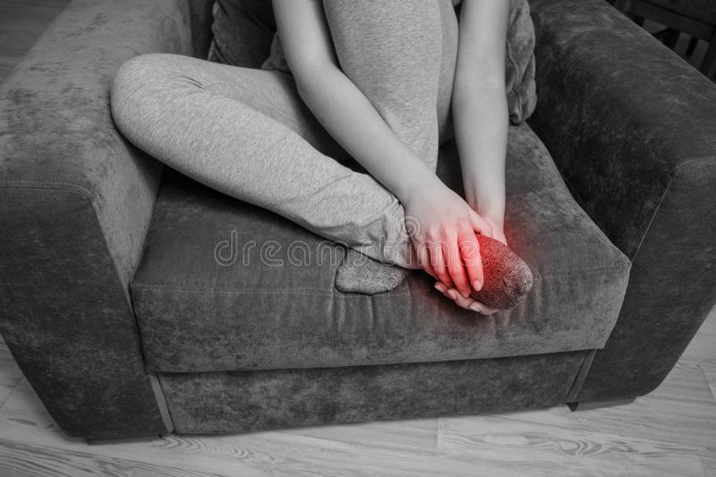 Pain in the foot, girl holds her hands to her feet, foot massage, cramp, muscular spasm, close-up royalty free stock images
