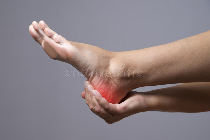 Pain in the foot. Massage of female feet. Pain in the human body on a gray background royalty free stock photography