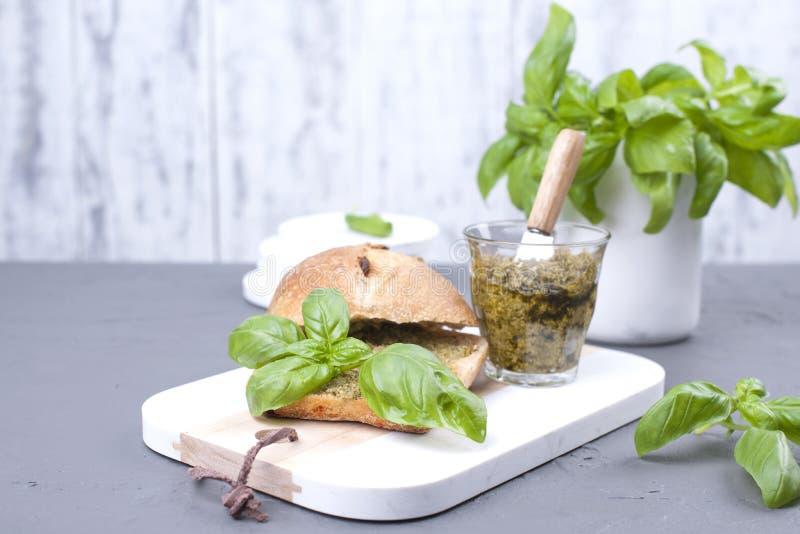 Pain frais avec de la sauce à pesto et basilic vert sur le conseil blanc Déjeuner sain délicieux L'espace libre pour le texte Cop photo stock