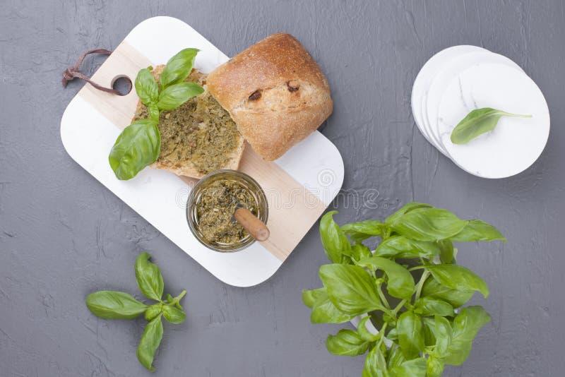 Pain frais avec de la sauce à pesto et basilic vert sur le conseil blanc Déjeuner sain délicieux L'espace libre pour le texte Vue images stock
