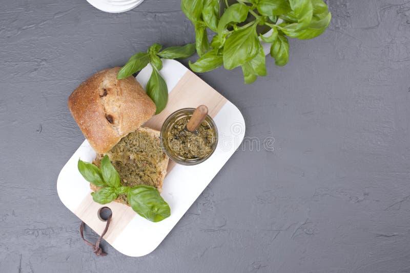 Pain frais avec de la sauce à pesto et basilic vert sur le conseil blanc Déjeuner sain délicieux L'espace libre pour le texte Vue image libre de droits