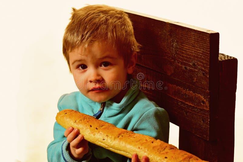 Pain frais Baguette française fraîche de prise de petit enfant La nourriture fraîche est les meilleurs produits frais de boulange images libres de droits