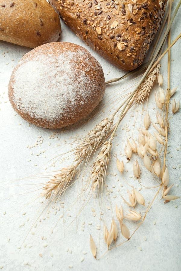 Pain frais d'or de travail manuel avec l'oreille de blé sur la table blanche photographie stock libre de droits