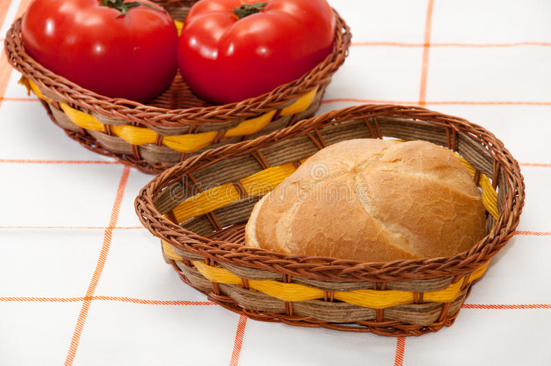 Pain frais et tomates dans les paniers en osier photographie stock