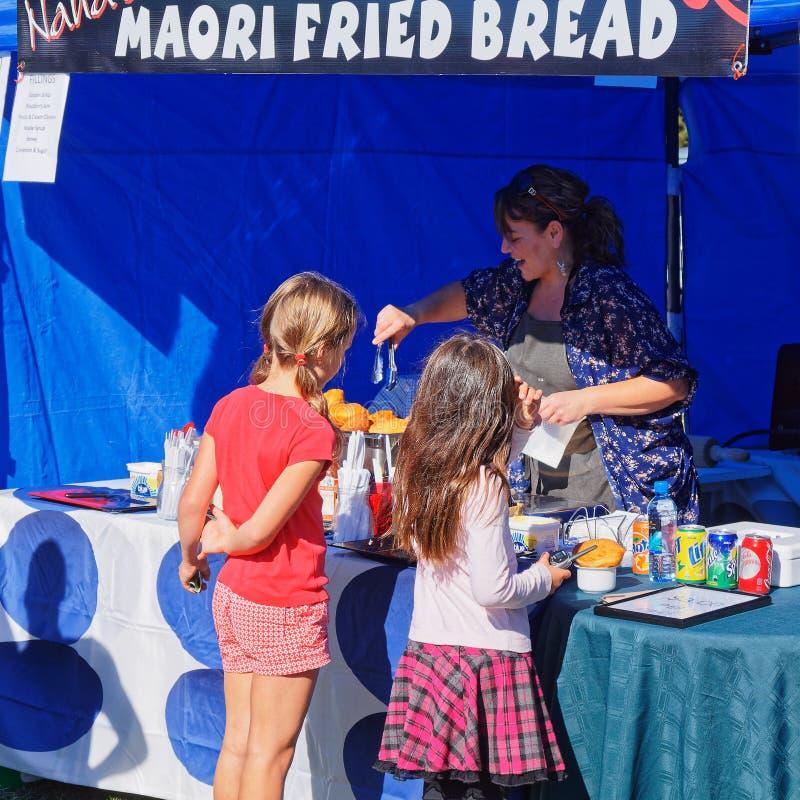 Pain frit maori étant préparé pour deux jeunes clients par un support gai de stalle du marché, Nouvelle-Zélande photos stock